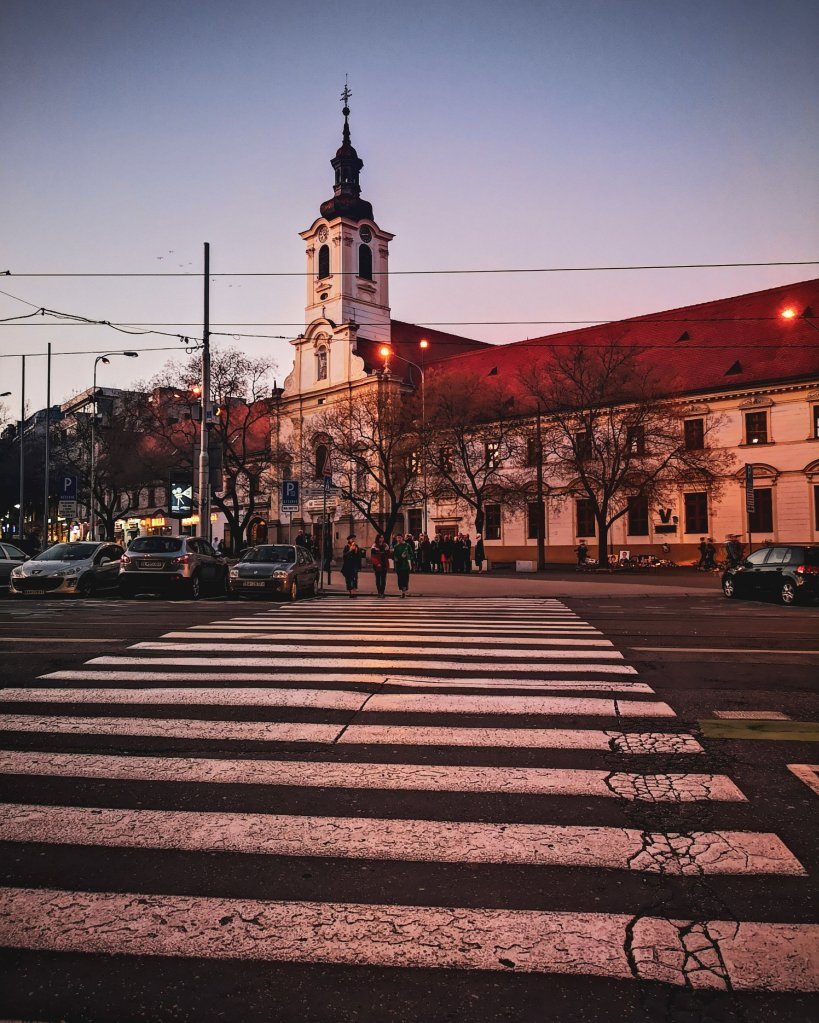 Zebra crossing with baroque building at night - Bratislava guide
