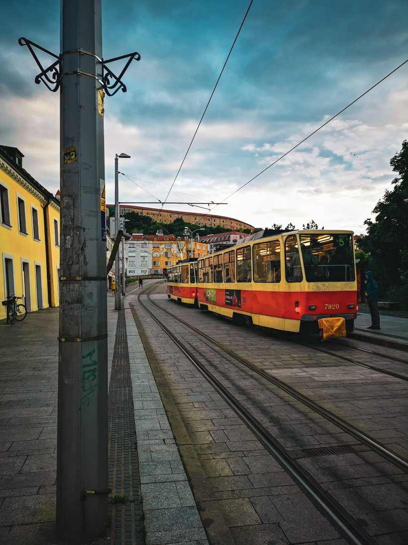 A yellow and red tram on a street in Bratislava - One and Two Day Itineraries To Bratislava + First Timer's Guide: Written By Locals!